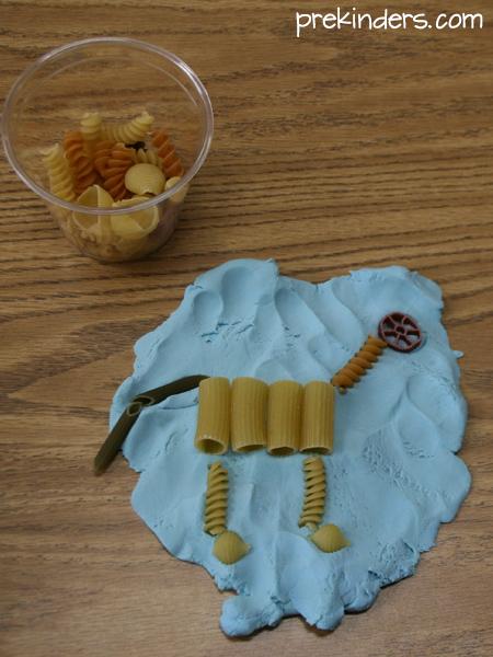 DIY Dinosaur Skeleton Fossil with Pasta over Soft Dough