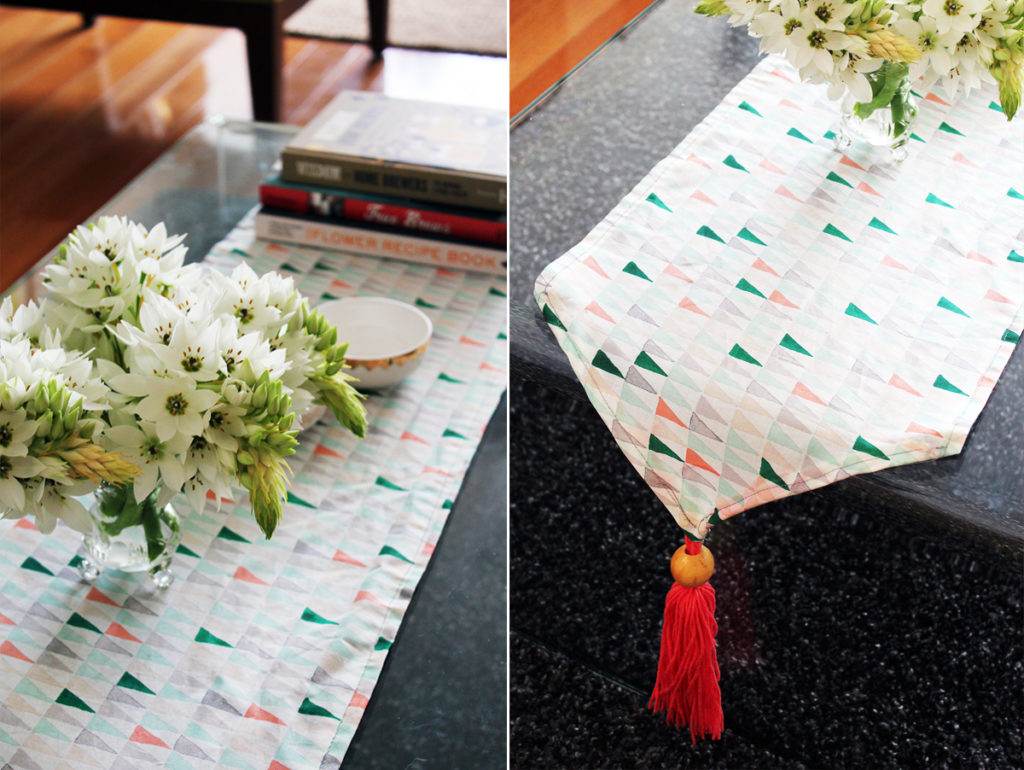 DIY Tasseled Table Runner with a Fancy Wooden Ball Decor Beneath The Cotton Made Base
