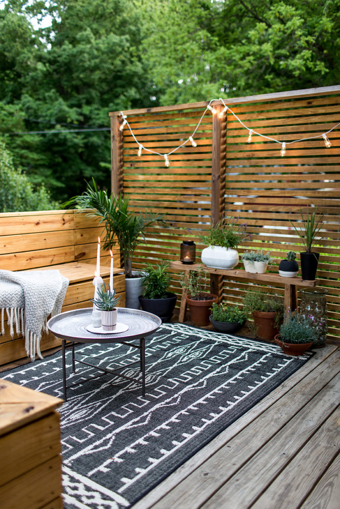 An Outdoor Renovation with Large Geometric Rug and Rustic Seating Furniture with Hidden Storage