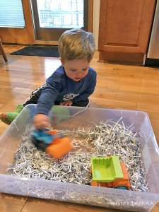 Construction Site Sensory Bin Activity with Toy Truck and Roughly Shredded Paper Scraps