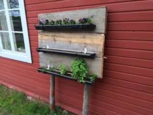Uniquely Made Vertical Herb Gardening with Narrow Planters Hanging on Rustic Wooden Board Base