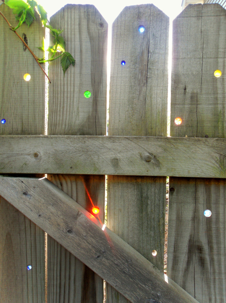 Garden Art on The Cheap DIY: Glass Marbles in Fence for A Sparkling Garden View