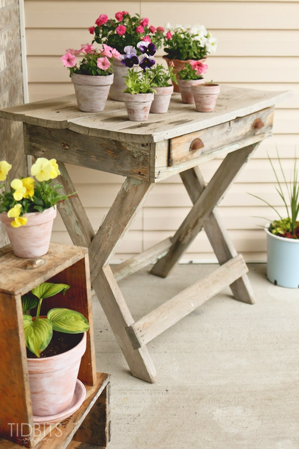 Summer Front Porch Decor Idea with WhitewashedTerra Cotta Pot And A Rustic Wooden Plant-Holder