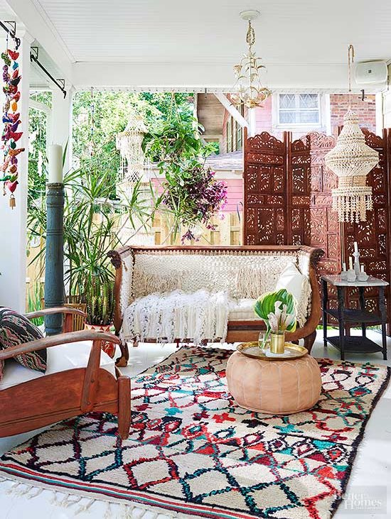 A Classic Front Porch Designing Idea with Wooden Furniture, Colorful Dhurrie, and Large Chandeliers