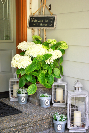 A Flowery Front Porch Decor Idea with Bushier Planters and Wire-Lanterns to Boost Your Curb Appeal