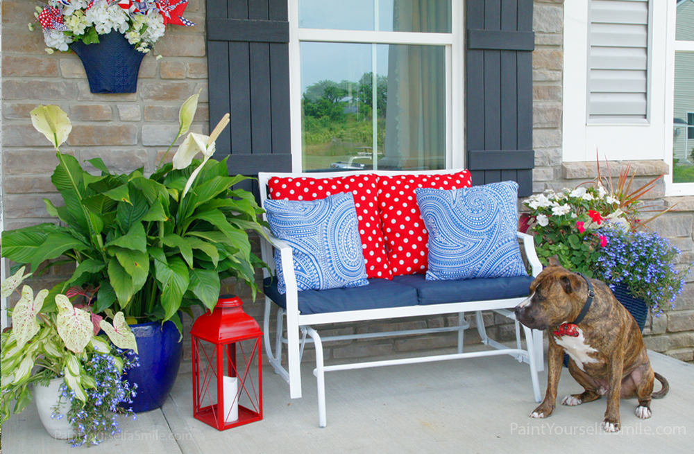 Welcome Home Porch Décor with Bold Color Strokes in Furniture, Cushions, and Flower Decors