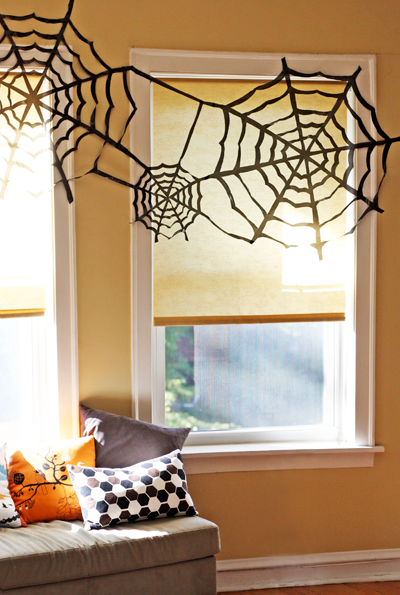 Do this super cheap Halloween spiderweb wall decor with black trash bags